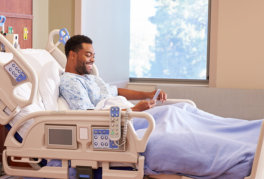 Male patient in hospital bed using cellphone