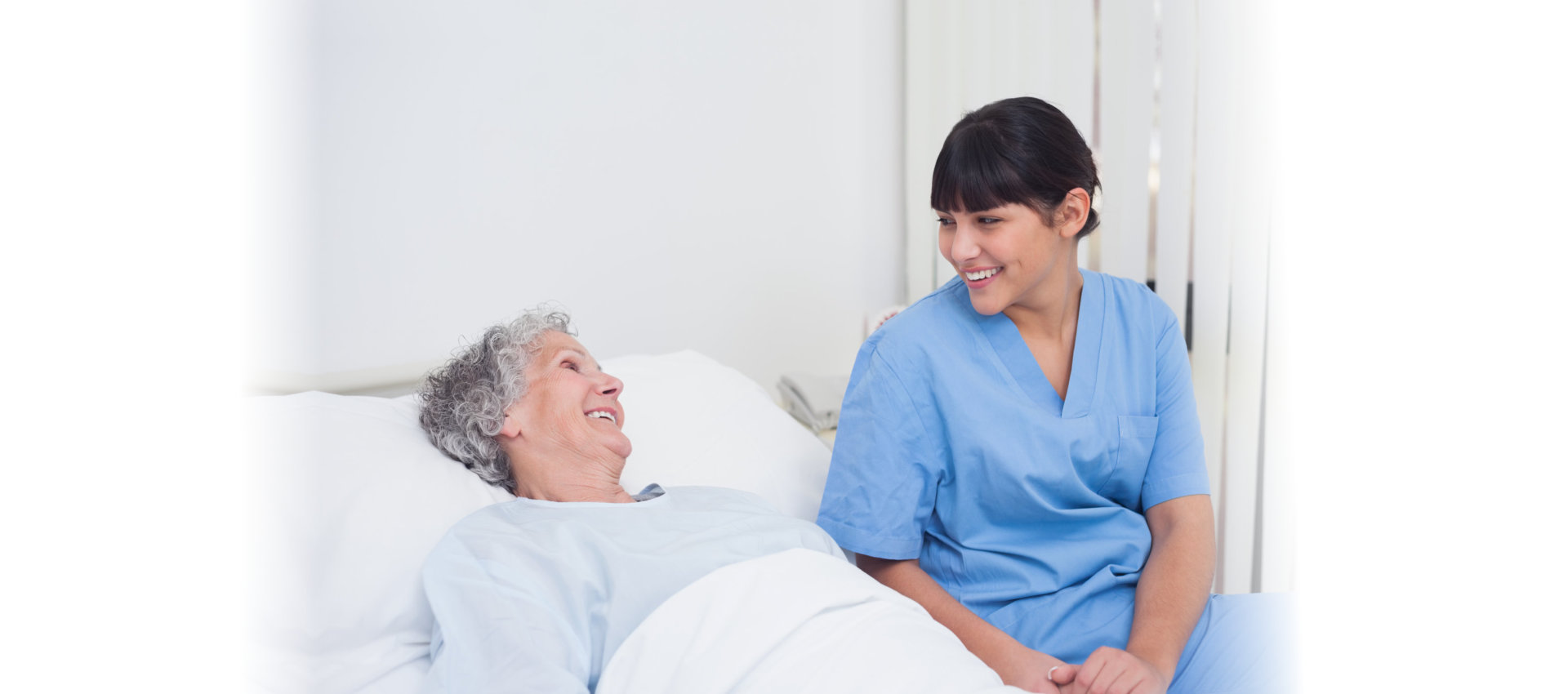 Nurse smiling to an elderly patient in hospital ward