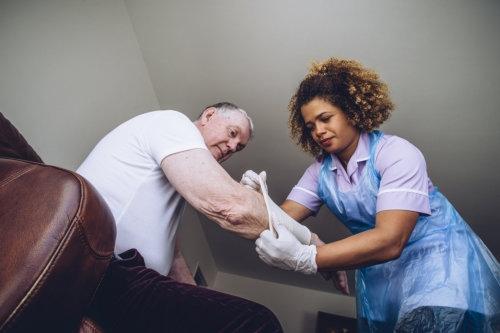 caregiving nurse putting a bandage on a senior mans arm